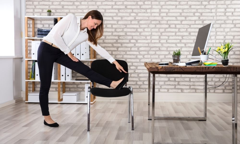 una donna fa lo stretching dello psoas con l'aiuto di una sedia