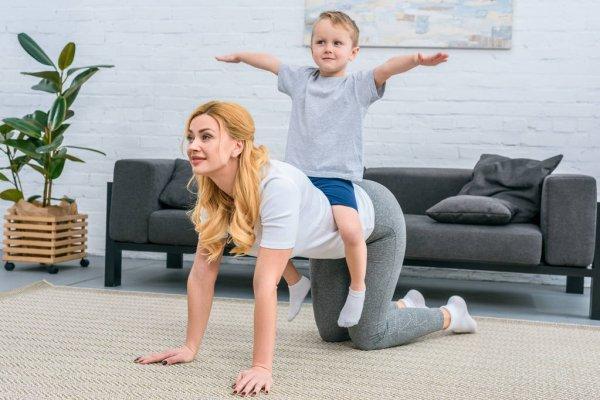 mamma con figlio sulla schiena fa l'esercizio del cane che fa pipì